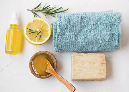 Natural skincare ingredients with manuka honey, lemon, essential oil, towel, rosemary herb and natural soap, healthy wellness and spa products , natural and homemade ingredients top view Standard-Bild - 118917409
