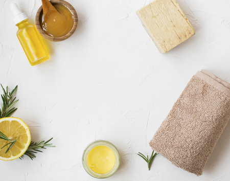 Natural skincare ingredients composition top view with copy space, manuka honey, lemon and rosemary herb, natural soap, towel, natural spa still life Standard-Bild - 118917412