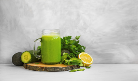 Green smoothie. Healthy green detox smoothie glass with spinach, lemon, cucumber, lemon and avocado, healthy organic food Standard-Bild - 118917183