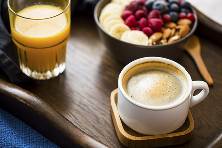 Breakfast meal with cup of coffee, glass of orange juice and a bowl of oatmeal with fresh berries, banana and almonds, healthy morning breakfast in wooden tray Standard-Bild - 118917190