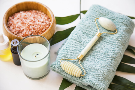 Spa still life with bath salt , jade roller, candle, towel and green leaf plant, spa and wellness setting Foto de archivo