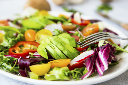 Healthy salad with bio organic vegetables, green vegan meal with avocado, pepper, radish, tomatoes, lettuce, cabbage, spring colorful salad closeup, clean eating concept Foto de archivo