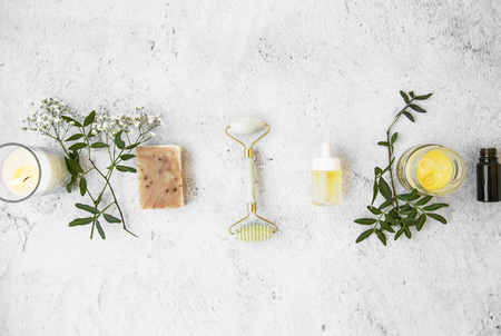 Natural organic skincare products on concrete background, top view, green natural skincare and beauty with  flowers, natural soap,jade roller, essential oils bottles, floral extracts and candle Foto de archivo