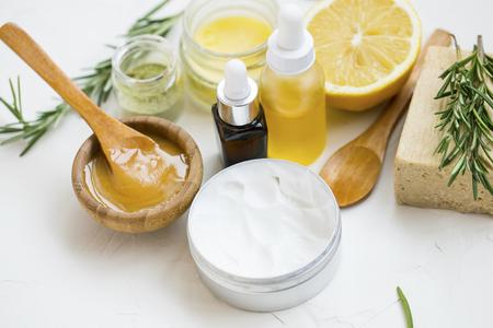 Ingredienti naturali spa organici con miele di manuka, bottiglia di olio essenziale, polvere di argilla, lozione per il corpo, sale da bagno, rami di rosmarino, sapone naturale, limone