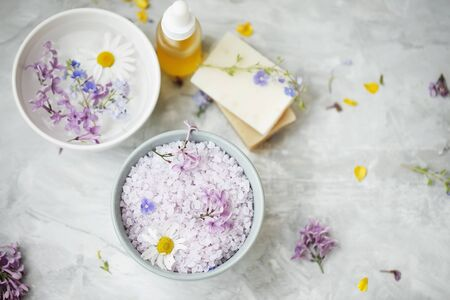 Spa still life with bath salt, spa and wellness treatments, top view of spa bath salts and flowers