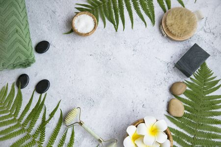 Green botanical spa flatlay with fern, charcoal soap, massage stones, frangipani flowers and bath salt , spa still life frame setting with copy space and body care products