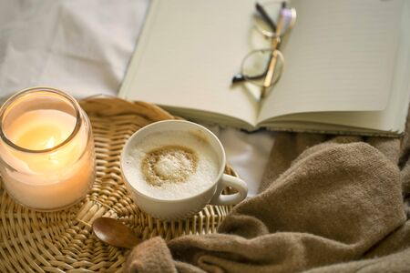 Cozy coffee cup, cappuccino with candle, notebook and cozy soft cardigan, morning bed coffee, vintage coffee cup, morning coffee still life Imagens