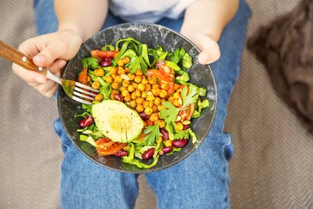 Clean eating, vegan healthy salad bowl , top view of woman holding salad bowl, plant based healthy diet with greens, salad, chickpeas and vegetables