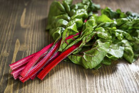 Mangold or red swiss chard leaves bunch on wooden board