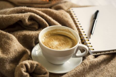 Cozy coffee cup with notebook and pen on cashmere cardigan, morning bed coffee, autumn coffee still life Imagens