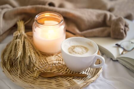 Cozy coffee cup, cappuccino with candle, notebook and cozy  morning bed coffee, vintage coffee cup, morning coffee still life