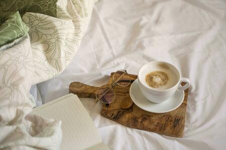 Coffee cup still life, morning coffee in bed, top view with notebook on wooden board, home indoor still life, autumn or winter morning coffee concept