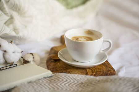 Cozy coffee cup cappuccino with notebook and pen on wooden board , morning bed coffee