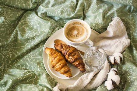 Morning breakfast with coffee cup and croissants in bed. Top view Imagens