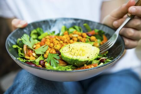 Clean eating, vegan healthy salad bowl , woman holding salad bowl, plant based healthy diet with greens, salad, chickpeas and vegetables Imagens
