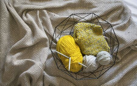 Basket with yarn and knitting neddles on cozy blanket, top view