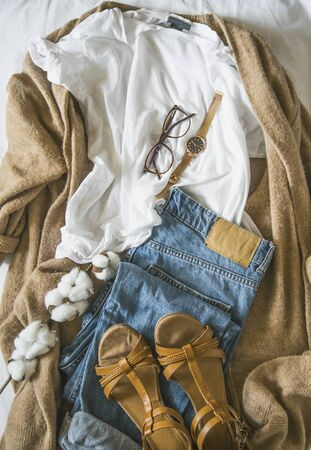 Cozy autumn clothing outfit with cardigan, jeans and sandals, top view of fall season outfit idea with glasses and watch accessory