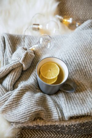 Fall warm tea cup, cup of lemon tea with warm cozy sweaters and scarf, cozy home interior autumn concept tea cup