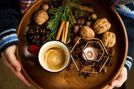 Rustic autumn wooden tray with coffee cup, candle, spices and nuts, autumn deco tray, woman holding wooden tray with fall deco and warm coffee, top view
