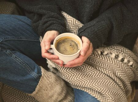 Autumn coffee cup with cozy blanket, fall deco warm home weekend with coffee cup,woman holding coffee cup with a blanket, autumn concept, cozy lifestyle rustic view