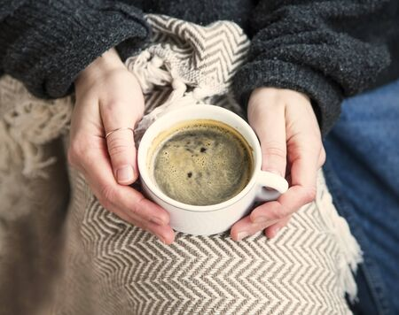 Interior cosy woman hands holding cup of coffee or chocolate with sweater and blanket, comfortable home winter or autumn lifestyle concept with hot drink, cosy winter weekend concept still life