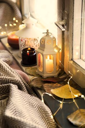 Winter lanterns decorations at window,cosy home interior decoration with candles, lanterns and blanket, cold season cozy home interior lifestyle concept with deco Zdjęcie Seryjne