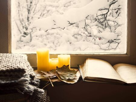 Winter cosy home interior still life at window,cosy home interior decoration with candles , knitting blankets and book, cold season cozy home interior lifestyle concept with deco