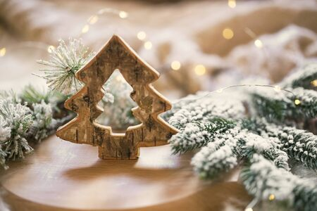 Wooden Christmas decoration with fir tree branches and festive lights