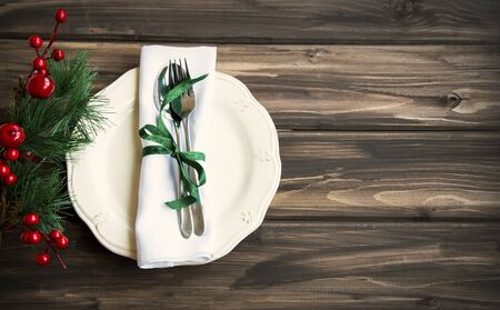 Festive Christmas table setting with white plate, tableware, ribbon on wooden rustic table background, top view Imagens