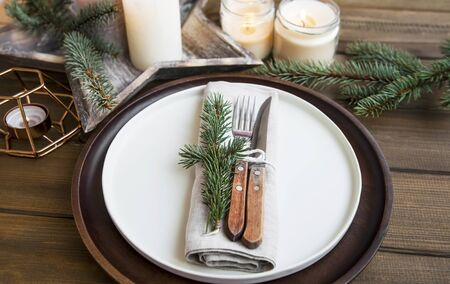 Festive Christmas table setting detail, with fr tree, wooden plate and candles on wooden table