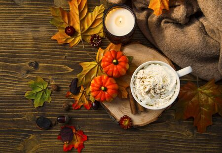 Spicy pumpkin latte with whipped cream cup and sweater, top view. Autumn coffee cup with pumpkin and cinnamon spice on wooden table with fall candle and decoration still life