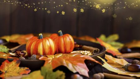 Autumn festive pumpkins decorations with dried leaves, indoor fall composition with pumpkins, leaves and festive lights Imagens