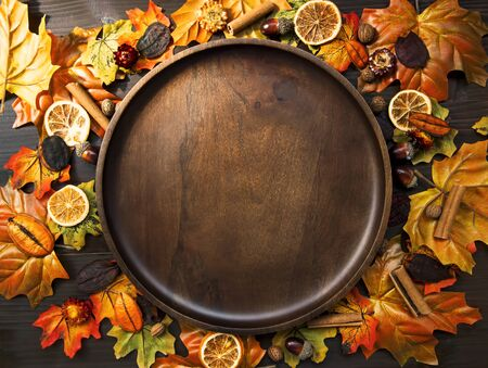 Autumn leaves frame composition with wooden plate, top view of fall decorations with copy space