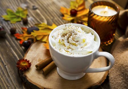 Spicy pumpkin latte with whipped cream. Autumn coffee cup with pumpkin and cinnamon spice on wooden table with fall candle and decoration still life Imagens