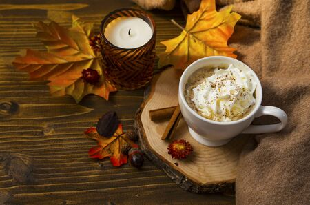 Spicy pumpkin latte with whipped cream cup and sweater. Autumn coffee cup with pumpkin and cinnamon spice on wooden table with fall candle and decoration still life Imagens