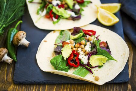 Vegan wraps with salad, chickpeas, vegetables and avocado, healthy tortilla rolls filled with vegetables , vegetarian dish