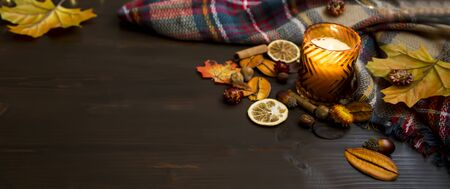 Autumn decorations with candle, scarf, dried leaves on wooden board