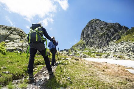 Hikers with backpacks and trekking sticks hiking to the mountain peak