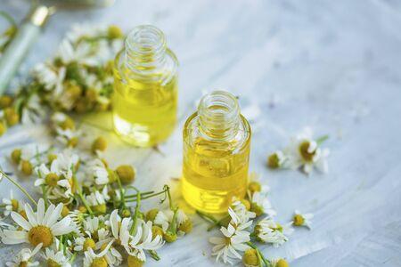 Olio di camomilla, bottiglie di olio essenziale di camomilla con fiori di camomilla
