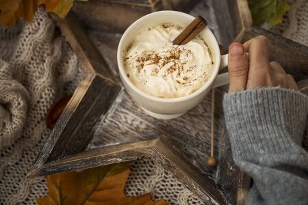 Hot chocolate cup with cream and cinnamon spice, woman holding cozy warm hot chocolate winter dessert drink Stock Photo