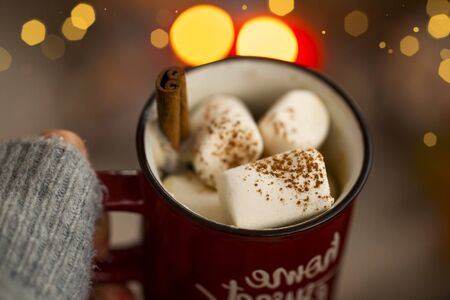 Hot chocolate cup with marshmallows candies and cinnamon spice, woman holding cozy warm hot chocolate winter dessert drink