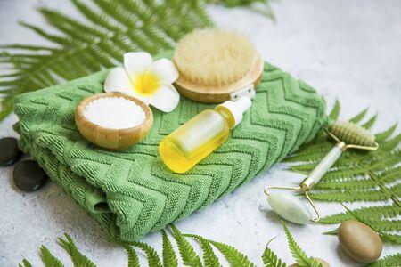 Entorno de bodegón de spa con botella de aceite, sal de baño, flores, piedras de masaje, toalla y hojas verdes, entorno de bienestar y spa