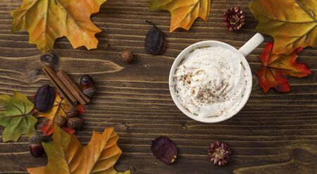 Coffee cup with cream and cinnamon on wooden autumn setting, top view with dried leaves and decorations
