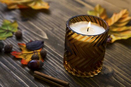 Spicy scented autumn candle  with fall dried leaves and spices on wooden background