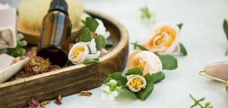 Spa still life setting with rose buds , wooden tray and oil bottle, natural clean vegan beauty products Reklamní fotografie