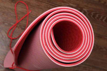 rubbery: Rolled red yoga mat on the wooden floor