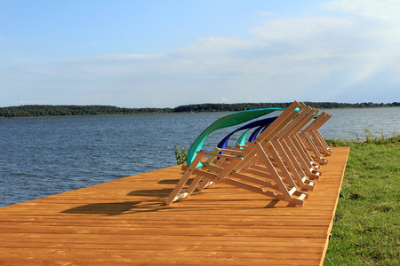 sunbeds: Sunbeds on wodden floor and water pool background