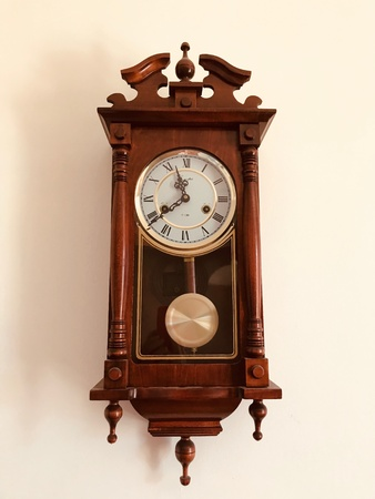 Old retro brown wooden clock hanging on the wall