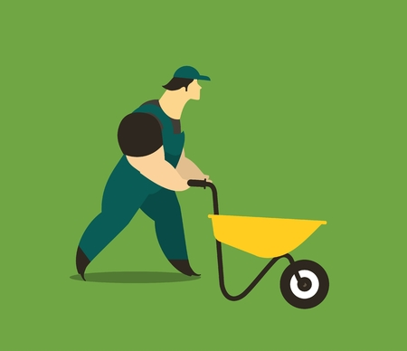 Adult man in a working form at work carries a wheelbarrow