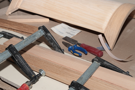 the detail of the wooden furniture facade is tightened into a clamp for repair on the desktop